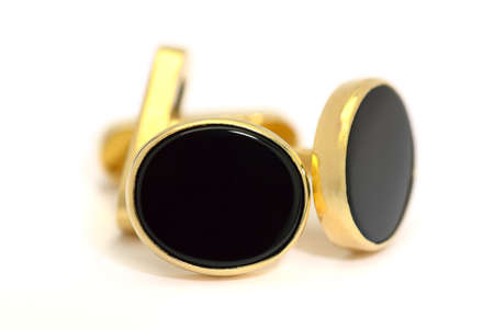 Pair of formal gold and oval black onyx cufflinks in closeup on a white background Stock Photo