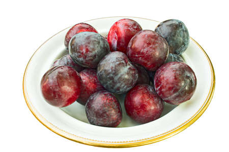 plateful: Bowl full of whole, ripe plums, covered with natural wax bloom