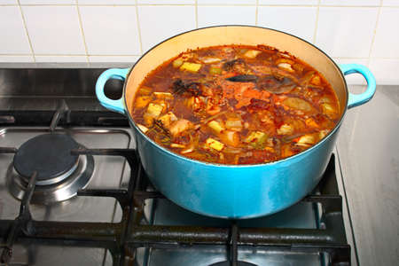 Stock simmering gently in a pot on a gas stove Stock Photo