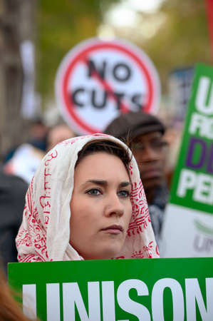 LONDON, ENGLAND, UK - NOVEMBER 30 2011: female protester, with Unison trades union sign, listening to speeches at the end of the N30 march, striking over public sector pensions, Victoria Embankment, London, England, UK, Europe