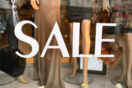 sale shop: Sale sign in a fashion shop window. Selective focus on lettering. Stock Photo