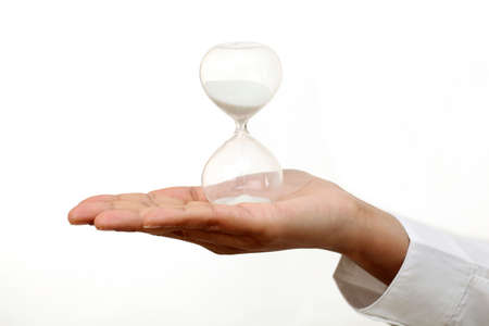 Business woman hand holding hourglass against white Stock Photo