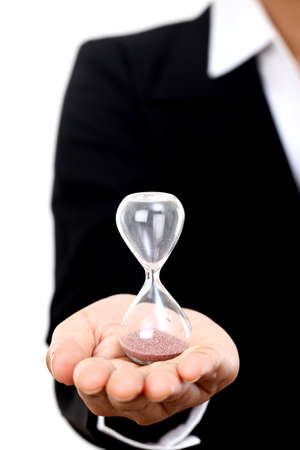 Business woman holding hourglass against white Stock Photo