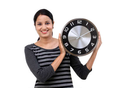 Beautiful young woman holding clock against white Stock Photo