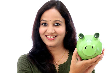 look latino: Young Indian Woman Saves Money in Piggy bank