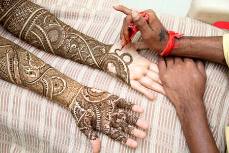 color tribal tattoo: Henna being applied to brides hand