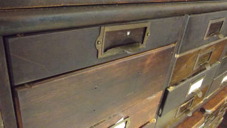 paper plates: antique wooden paper cabinet with drawers with metal name plates Stock Photo