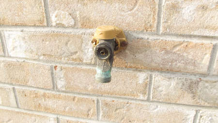 spigot: Water spigot with missing handle on brick wall Stock Photo