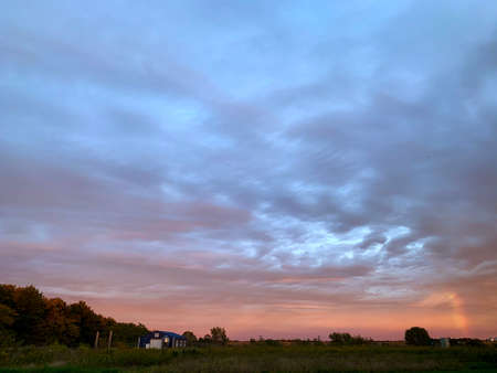 Pink and blue sunset over woodland farm