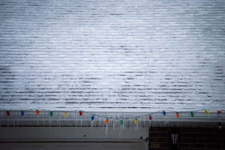 Icey Christmas lights hanging from snowy roof