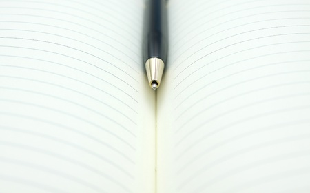 a pen in middle a book  photo
