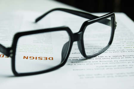 Glasses on open book and pen,Focus at word  DESIGN  Stock Photo