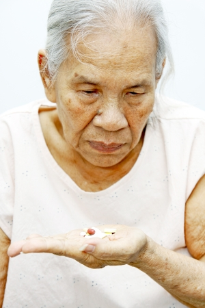 Old woman looking at pills in her hand