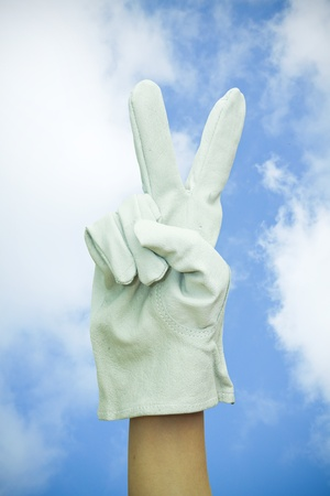 Hand with work glove making victory sign  on blue sky Stock Photo - 13712883
