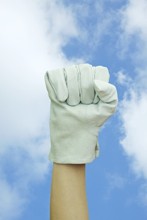 Hand with work glove Raised fist in blue sky  photo