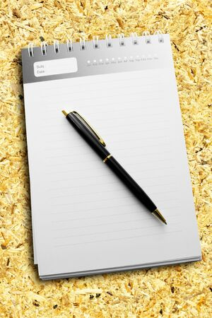 A pen on a diary with striped paper and all on the recycle compressed wood. Stock Photo - 14355796
