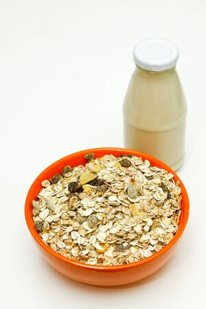 Orange bowl of cereal with a glass bottle of  milk. Stock Photo