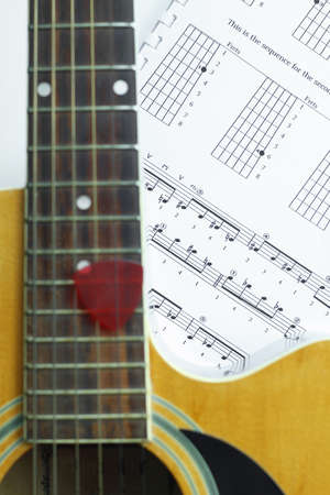 Acoustic Guitar on music note sheet ,focus at music note sheet.