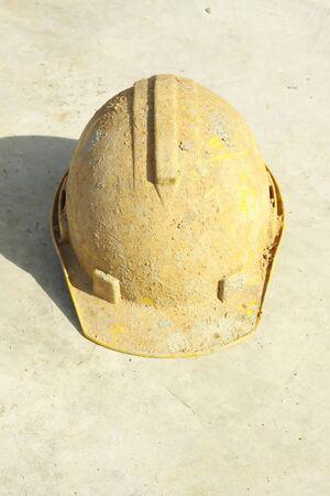 Dirty yellow hard hat on Concrete floor. photo