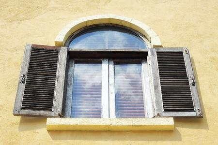 Old wooden window open on orange wall. photo