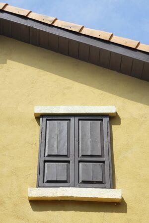 Old wooden window close on orange wall