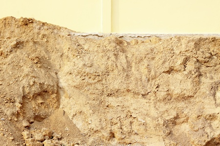Pile of dry soil at yellow wall photo