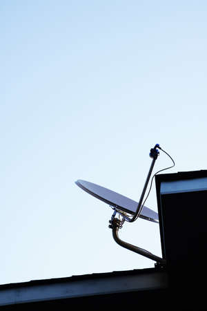 Satellite dish Antenna mounted on the roof with blue sky in the morning time photo