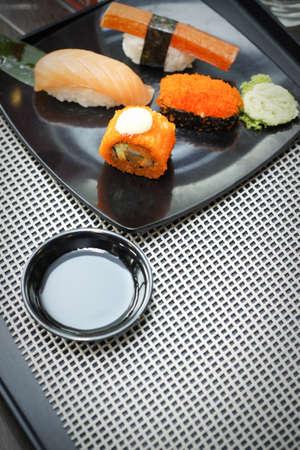 Sushi on black dish with Japanese sauce