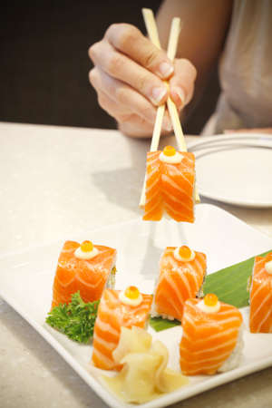 woman hand holding salmon sushi with chopsticks