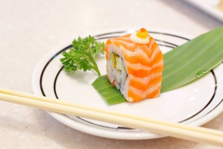 Sushi salmon roll on white dish with chopsticks photo