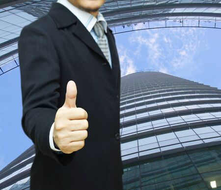 Businessman in suit with thumb up with office buildings in the background Stock Photo - 18320129