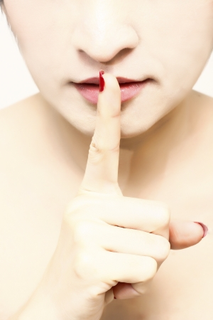 Close up women with her finger over her mouth Stock Photo