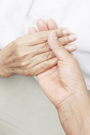 Hands of a younger woman holding the hand of an elderly woman.