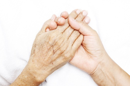 Hands of a woman holding the hand of an elderly woman. Stock Photo