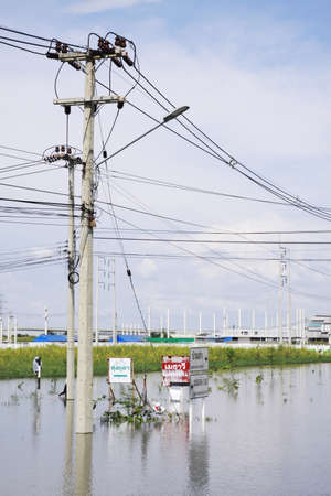 inconvenient: CHONBURI THAILAND - Oct 18,2013    Traffic signs and Electricity post submerged  Water flooding attack to Amata Nakorn Industrial Estate in Chonburi Thailand