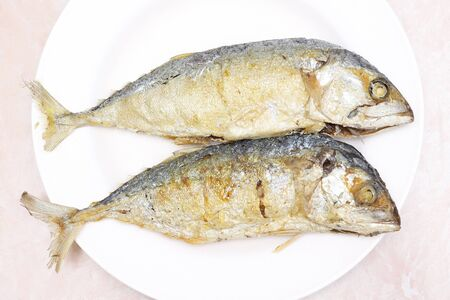 two fried mackerel fishes on white plate