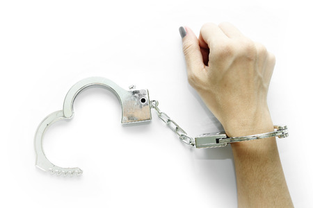 Right hand of Woman with handcuffs on white background photo