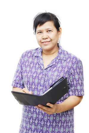 senior smiling woman holding pen and notebook