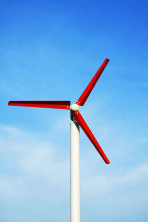 Red wind turbine working with blue sky
