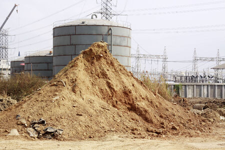 Pile of dry soil and sand in front of big Industrial tanks  Editorial