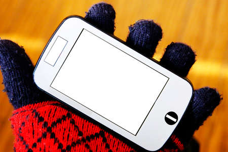 Hand with red glove holding the smart phone