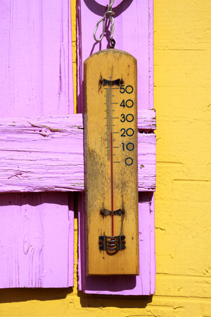 Old thermometer hang on a wooden background Stock Photo