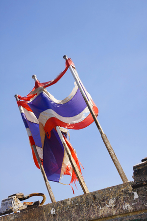 photo of Tattered Thailand flag over blue sky Stock Photo