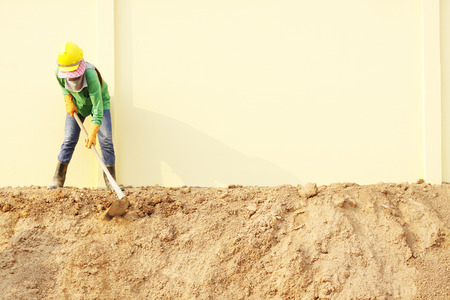 hoe: Laborer digging with hoe on construction site Stock Photo