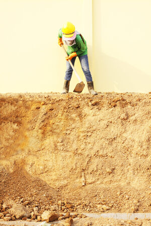 Laborer digging with hoe on construction site Stock Photo