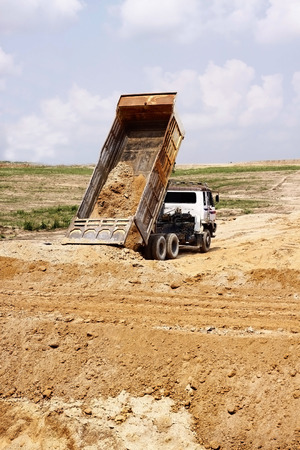 sand quarry: Heavy dump truck unloading soil on the sand at a construction site