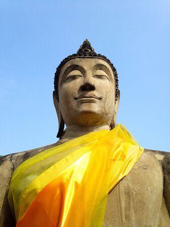 Stone statue of buddha against blue sky at Wat Yai Chai Mongkol in Ayutthaya, Thailand