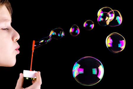burbujas de jabon: Niño soplando burbujas en el fondo negro