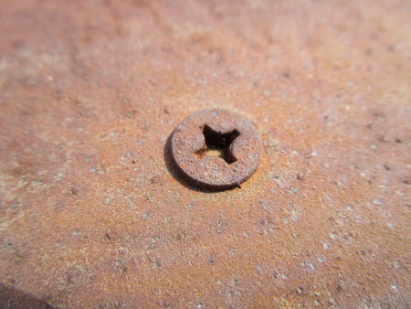 Old rusty metal plate with self-tapping screwed into it