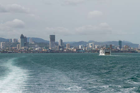 lite: Skyline View of Cebu City from Lite Ferry with Wake Trailing in Water Behind Boat on Island of Cebu, Philippines